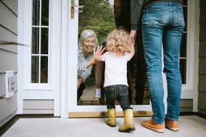 A grandmother and granddaughter greet each other through a closed door during the COVID-19 pandemic representing how you may benefit from family counseling in Hinsdale.